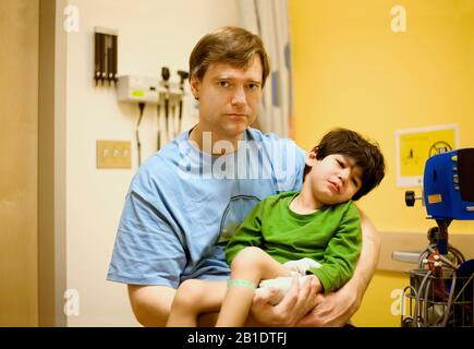Worried Caucasian father holding biracial sick disabled son in hospital waiting room - Stock Photo