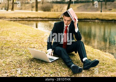young guy tired of work. man in a suit running on the nature near the lake. Generations Y, millennials - Stock Photo