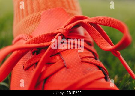Close up of a soccer player's cleat on grass field. Red sports shoes with tied shoelaces - Stock Photo