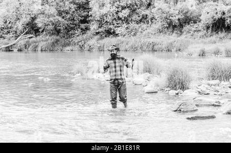 Fisher masculine hobby. Fish on hook. Brutal man stand in river water. Man bearded fisher. Fishing requires to be mindful and fully present in moment. Fisher fishing equipment. Rest and recreation. - Stock Photo