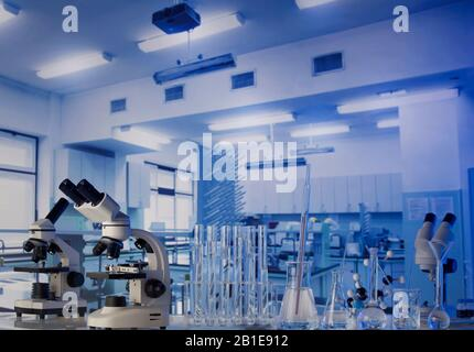Science laboratory. Beakers, test-tubes and microscope on glass table in the laboratory.