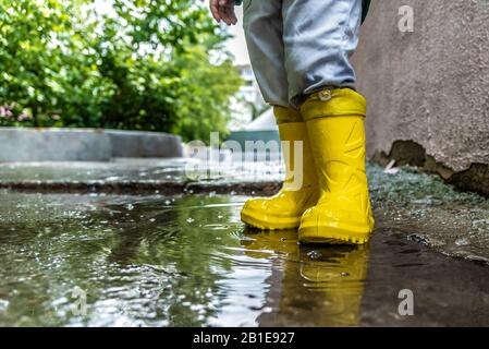 little baby is standing in a puddle in rubber boots