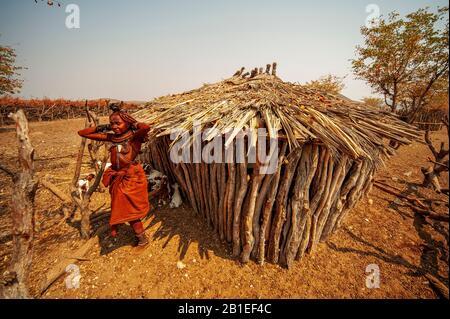 Himba woman with traditional clothes near his primitive hut at his village near Epupa Falls, Namibia - Stock Photo