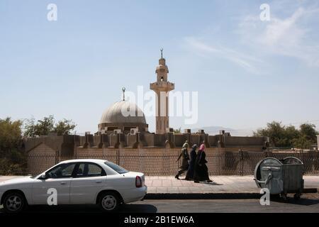 Aqaba, Jordan, April 27, 2009: Women walk on the sidewalk of a road, passing a mosque in Aqaba, Jordan. - Stock Photo