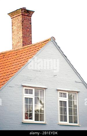 Small piece of living house with chimney, brick painted wall and new plastic windows. Tile roof. - Stock Photo