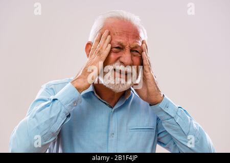 Portrait of senior man who is having headache. - Stock Photo