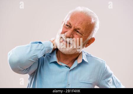 Portrait of senior man who is having pain in neck. - Stock Photo