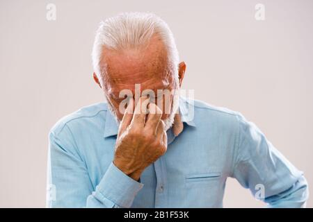 Portrait of senior man who is having pain in sinus. - Stock Photo