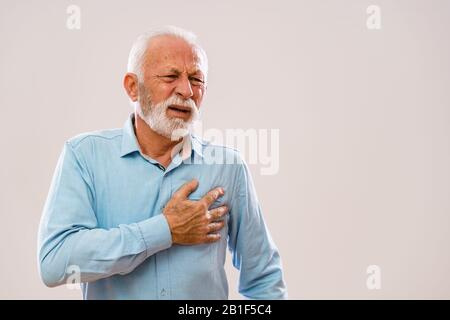 Portrait of senior man who is having pain in his chest. - Stock Photo