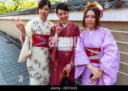 Kyoto Japan. Women dressed with traditional kimono garment in the streets of Kyoto - Stock Photo