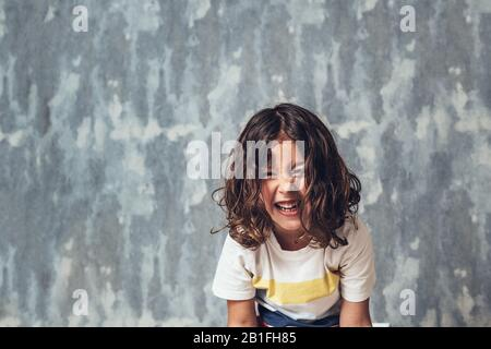 portrait of a happy little girl laughing out loud on a blue background, happy childhood and lifestyle concept, copy space for text