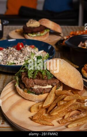 Variety of dishes on wooden table. Restaurant menu. Burgers and salad. - Stock Photo