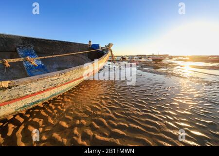 Wooden boats at low tide in Cadiz harbour in the evening sun. - Stock Photo