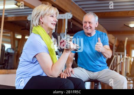 Senior woman in the gym exercising with dumbbells for fitness