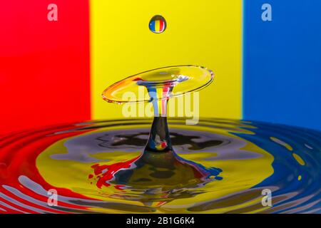 Abstract photograph of a water drop collision created with two water drops splashing together isolated against a red, yellow and blue striped backgrou - Stock Photo