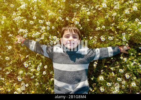 child smiling happy among the daisies in springtime day - Stock Photo