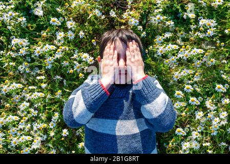 child lying with closed eyes among the daisies in a sunny springtime day - Stock Photo