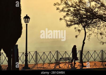 Silhouette of a lonely woman walking through the park with a special sunset light - Stock Photo