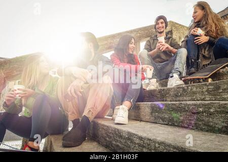 Happy friends drinking paper cup coffee take away on city staircase - Young people having fun outdoor in university break - Friendship concept - Warm - Stock Photo