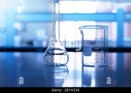 beaker and volumetric flask on chemistry science blue laboratory table background - Stock Photo