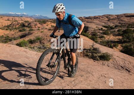 February 25, 2020: The Bureau of Land Management announced February 24 that it would remove two parcels of land within the Sand Flats Special Recreation Area near Moab, Utah, from an upcoming oil and gas lease sale. The plan would have allowed exploratory drilling under the Slickrock Trail, one of the world's most popular mountain biking destinations. Pictured: Apr 5, 2015 - Moab, Utah, U.S. - Mountain biker TIM LANE riding the red sandstone of the famous slickrock trail with La Sal mountains and snow behind. Moab sports some of the most spectacular and challenging mountain biking anywhere. Po - Stock Photo