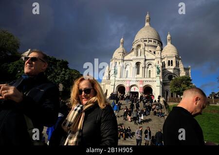 Basilica of Sacre-Coeur in Montmartre.Basilique du Sacré Cœur de Montmartrewith tourists in foreground.Paris.France - Stock Photo