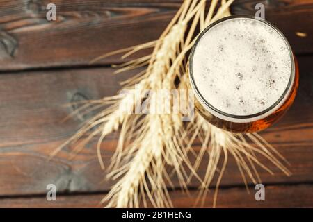 Glass beer on wood background. Creative photo.