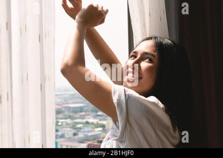 Young diverse woman yawning and stretching out of apartment block window - Sleepy head tired millennial Asian girl waking up late to bright morning sunshine - Weekend, lazy and fresh concept - Stock Photo