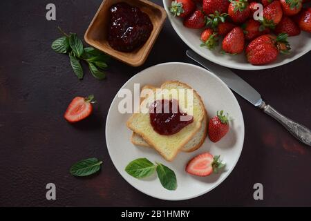Toasts with strawberry jam for breakfast, rustic style