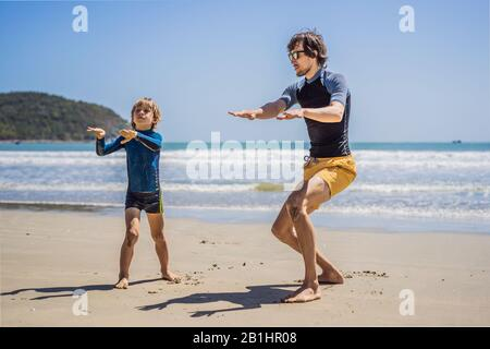 Father or instructor teaching his son how to surf in the sea on vacation or holiday. Travel and sports with children concept. Surfing lesson for kids - Stock Photo