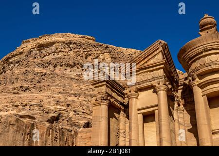 Sunny cloudless day close-up detailed view of the stunning Ad-Deir in the ancient city of Petra, Jordan. Ad-Deir or The Monastery. Petra complex and tourist attraction, Hashemite Kingdom of Jordan - Stock Photo
