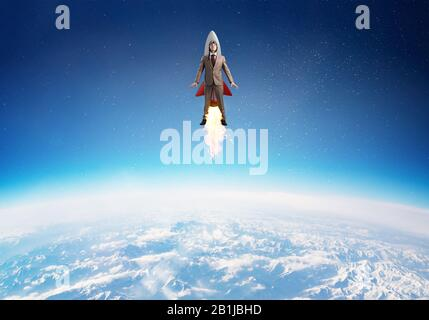 Businessman in aviator hat flying on rocket - Stock Photo
