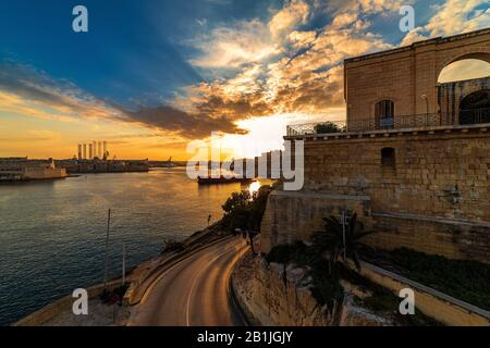 Beautiful sunset over Mediterranean sea and bay of Malta as seen from Valletta. - Stock Photo