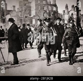 An Irish nationalist is led under escort by British oldiers to Dublin Castle following the Easter Rising of 1916, an armed insurrection in Ireland during Easter Week, April 1916. It was launched by Irish republicans to end British rule in Ireland and establish an independent Irish Republic while the United Kingdom was fighting the First World War. It was the first armed action of the Irish revolutionary period. Sixteen of the Rising's leaders were executed in May 1916, but subsequent  political developments ultimately contributed to Irish independence. - Stock Photo