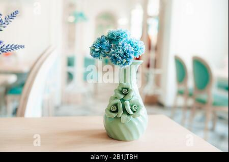 A small mint colored vase with blue cornflowers on a wooden table in a bright spacious room with blue chairs - Stock Photo