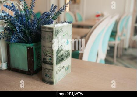 Vintage old book with a picture of the Colosseum and a vase of lavender. The interior of a bright and spacious room with blue chairs. - Stock Photo