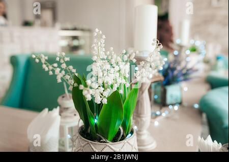 White lilies of the valley spring flowers with green leaves in the light interior of the room on the background of blue garlands and bokeh. - Stock Photo