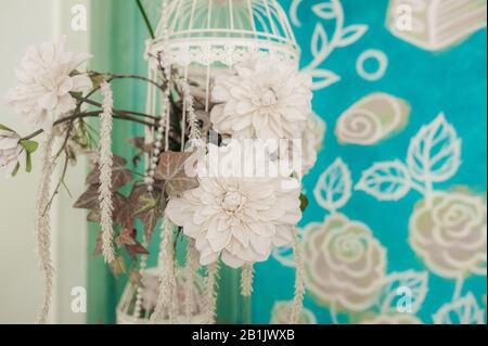 Wall decor in the room, white artificial flowers in a hanging vase on a background of painted blue flower. - Stock Photo