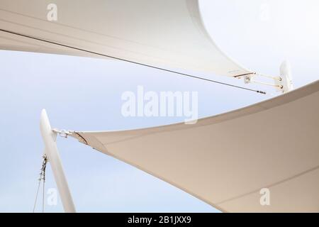 White awnings in sails shape under bright blue sky background - Stock Photo