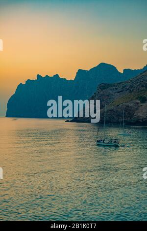 Sunrise Behind Dramatic Cliffs With Sailboats on the Mediterranean Sea - Stock Photo