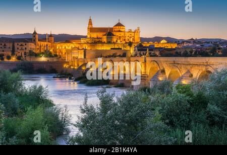 Panoramic night sight in Cordoba, with the Roman Bridge and Mezquita on the Guadalquivir River. Andalusia, Spain. - Stock Photo