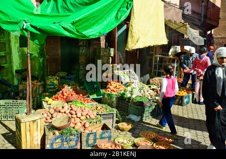 Marrakesh, Morocco - November 22nd 2014: Unidentified people shopping on market with grocery, vegetables and fruits - Stock Photo