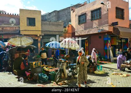 Marrakesh, Morocco - November 22nd 2014: Unidentified people on street market with different goods and food - Stock Photo