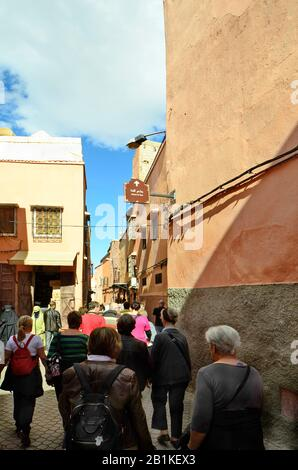 Marrakesh, Morocco - November 22nd 2014: Group of unidentified tourists by sightseeing in narrow street in old precinct, woman with traditional veil - Stock Photo