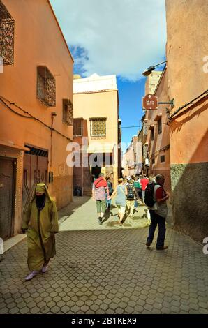 Marrakesh, Morocco - November 22nd 2014: Unidentified tourists by sighseeing in narrow street in the old precinct and woman in traditional kaftan with - Stock Photo