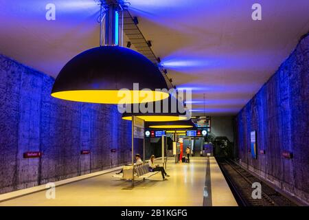 Munich, Germany – July 1, 2016. Interior view of Westfriedhof U-Bahn station on the U1 line of the Munich U-Bahn system, with people and information b - Stock Photo