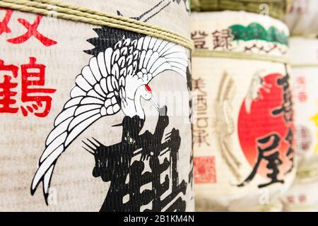 Sake barrels covered in Japanese art, including a flying stork, at Kushida-jinja,  a Shinto shrine. Hakata-ku Old Town, Fukuoka