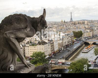 View of the Paris cityscape, including the Eiffel Tower and the River Seine, from one of the towers of Notre-Dame, with a stone carved Gargoyle in the - Stock Photo