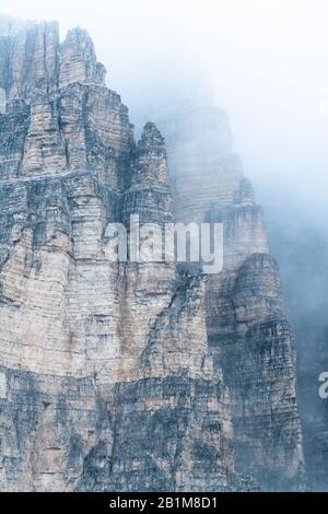 Fog over the tall rocks of Tre Cime di Lavaredo, Sesto Dolomites, South Tyrol, Italy - Stock Photo