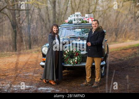 Cheerful young couple dressed in warm clothes with sparklers in hands looking at camera while standing by the retro car with presents on the roof - Stock Photo